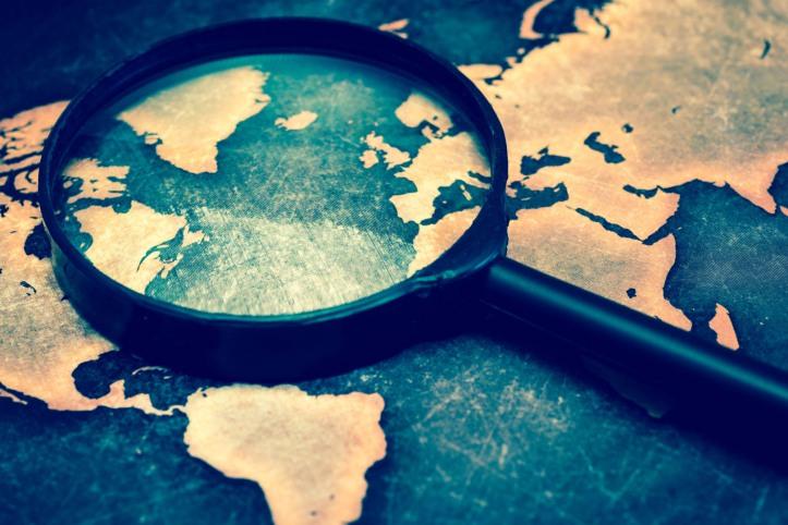 Magnifying lens on grunge world map